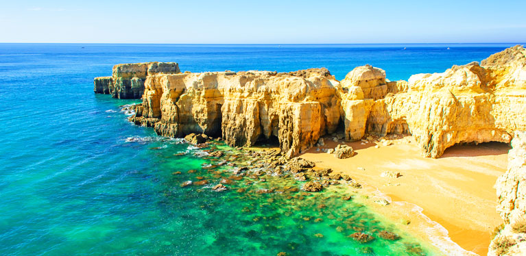 sunny image of Algarve coast with clear blue waters